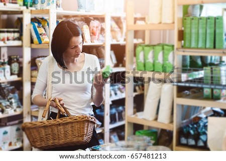 Woman choosing products in ecological shop with healthy food and reading product information on label #657481213