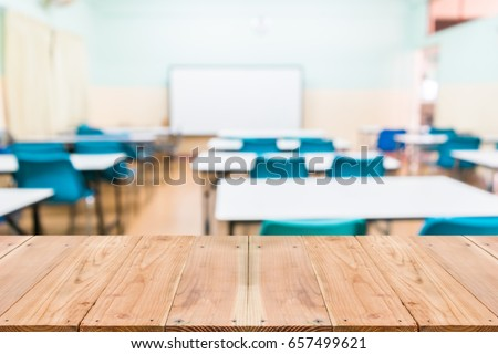 Look out from the table, blur image of empty classroom as background. Royalty-Free Stock Photo #657499621