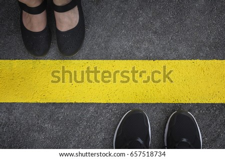 Legs of a couple standing opposite each other divided by the yellow asphalt line top view Royalty-Free Stock Photo #657518734