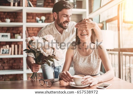 Surprise! Beautiful romantic couple in cafe. Young man is presenting flowers to his beloved. Feel of happiness. Royalty-Free Stock Photo #657538972