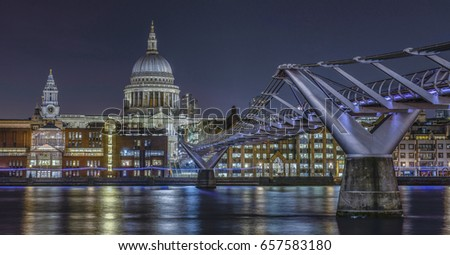 London skyline with Millennium Bridge and St Paul's Cathedral on River Thames at night, England