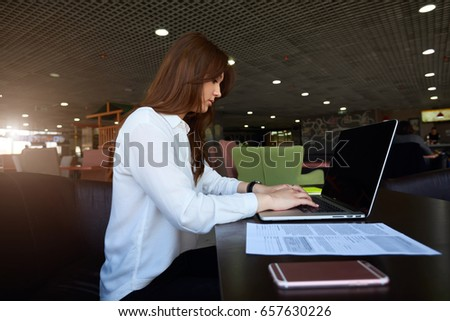 Creative beautiful female graphic designer writing email to chief about work improvements on laptop computer with copy space screen for your promotional content sitting at table
