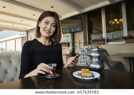 Portrait of positive attractive Chinese woman looking at camera while texting feedback for product in popular website through telephone during sitting at wooden table in cafe