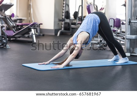 Young attractive woman practicing yoga, standing in Downward facing dog exercise #657681967