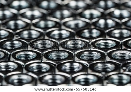 Nuts and bolts metal fasteners. Hexagon metal nuts arranges in a tessellation macro, with dramatic lighting to illustrate engineering or construction expertise. Royalty-Free Stock Photo #657683146