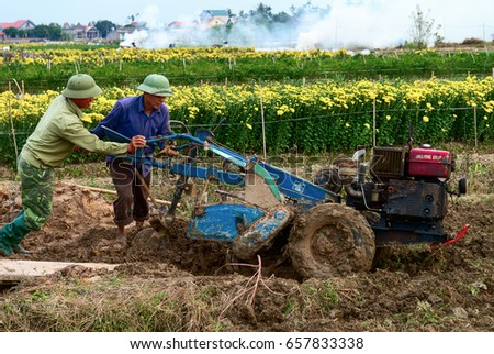 HAI DUONG, Vietnam, January 15, 2017 man, plowing, planting flowers in the spring, suburban Hai Duong, Vietnam #657833338