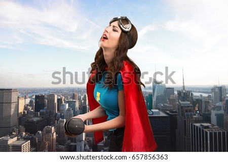 Pretty superhero girl making weightlifting with the city in the background #657856363