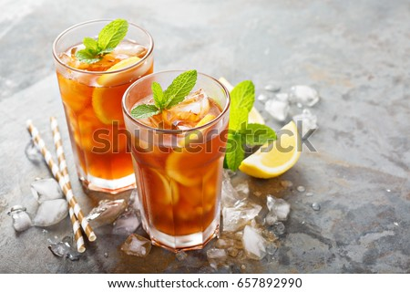 Traditional iced tea with lemon and ice in tall glasses #657892990