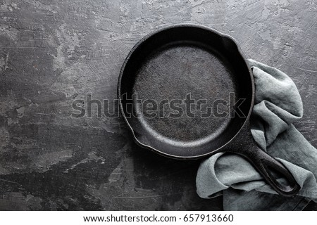 Empty cast iron frying pan on dark grey culinary background, view from above #657913660