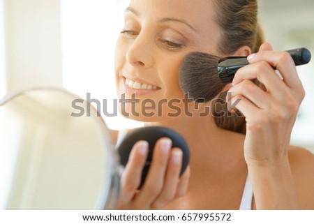 Portrait of beautiful woman putting makeup on #657995572
