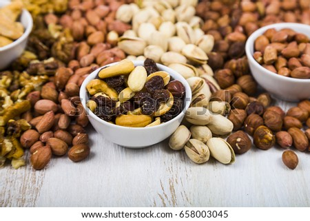 Nuts on a  wooden table. Different kinds of tasty and healthy nuts #658003045