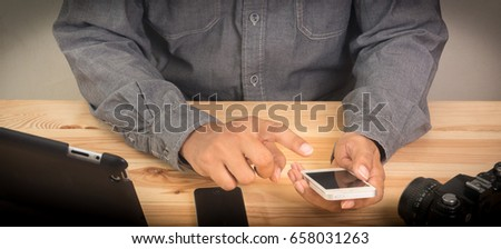 businessman holding smart phone and wood desktop in workplace. #658031263