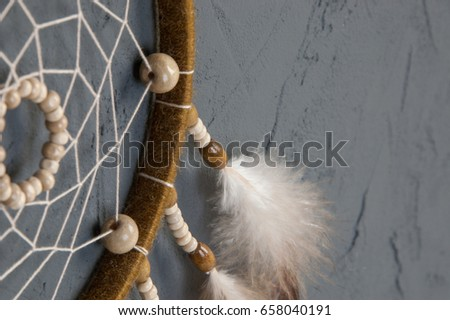 Olive beige dream catcher close up on dark gray textured background. Texture of concrete, copy space for text #658040191