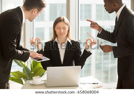 Beautiful businesswoman meditating at workplace, ignoring work, not listening to annoying clients or bothering colleagues talking to her, sitting at office desk with eyes closed, keep calm, no stress Royalty-Free Stock Photo #658068004
