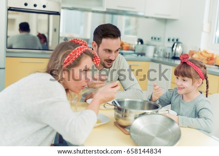 Happy mother, father and little girl eating soup at home. #658144834