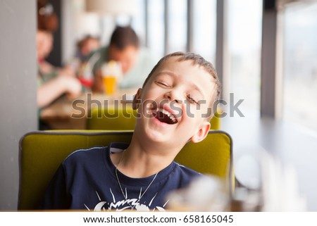 boy is laughing loudly in cafe #658165045