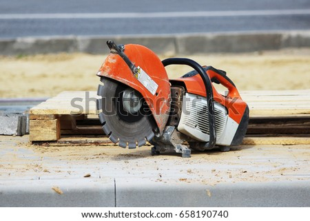 A circular saw for sawing a curb plate lies near a wooden pallet when building a parking lot for tourist buses. #658190740
