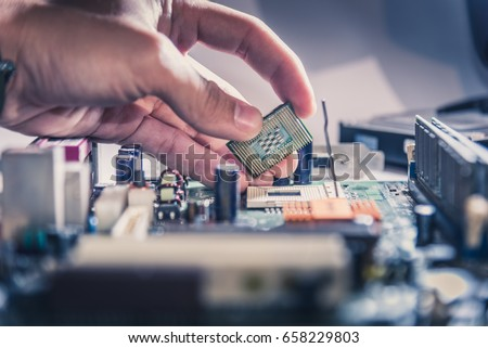 The technician is putting the CPU on the socket of the computer motherboard. #658229803