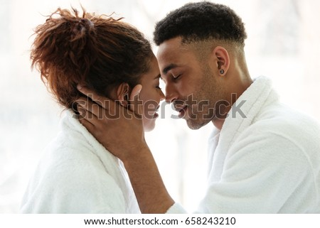 Picture of young african loving couple standing indoors at home and looking aside while hugging.
