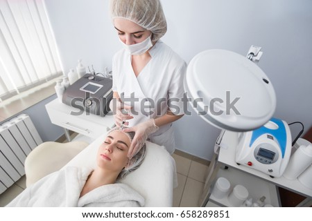 Woman gets injection in her face. Beauty woman giving botox injections. Young woman gets beauty facial injections in the cosmetology salon. Face aging injection. Aesthetic Medicine, Cosmetology #658289851