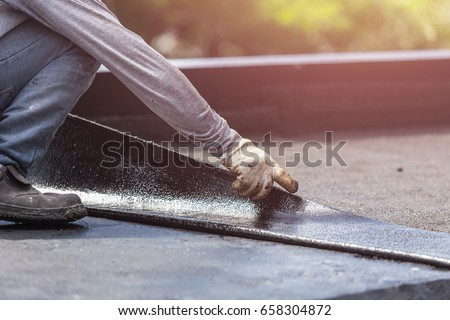 Asia worker installing tar foil on the rooftop of building. Waterproof system by gas and fire torching #658304872