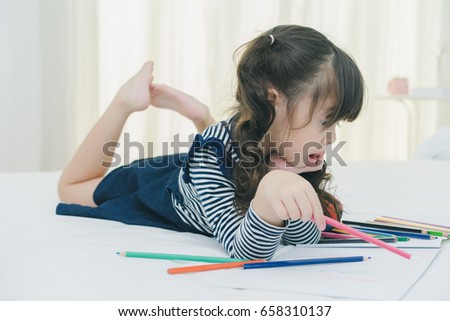 A little cute girl enjoy drawing into the book by colorful pastel with mother on the white bed in the bedroom, education time at home, happy family concept  #658310137
