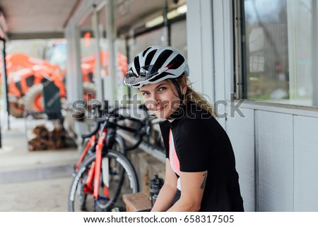 Tired but happy, exhausted after long training ride female rider smiles into camera in her helmet and lycra cycling kit, with professional road bikes in distance #658317505
