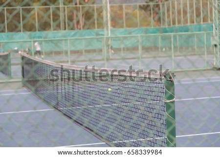 Views from the viewer through a steel mesh. Tennis court seating area. Tennis net in tennis court. #658339984