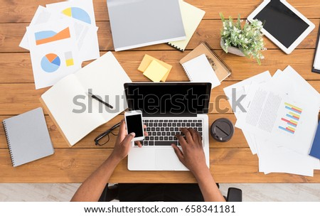 Office workspace top view. African-american businessman working at wooden desk, using laptop and various objects all around #658341181