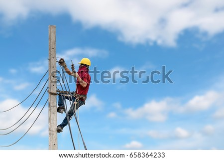 Electricians are climbing on electric poles to install power lines. #658364233