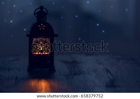 Small lantern with a burning candle on the table with the stars.Magical beauty #658379752