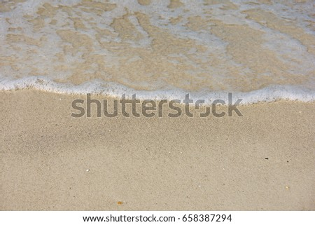 frothy ocean salt water on sandy beach #658387294