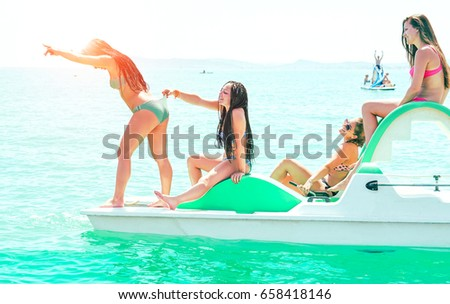 Happy friends girls having fun on rental boat on summer vacation - Cheerful young women making funny bathing jokes on pedalos sea excursion day - Playful holiday concept and teenage friendship #658418146