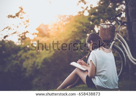 beautiful woman writing into her diary, in the park Royalty-Free Stock Photo #658438873