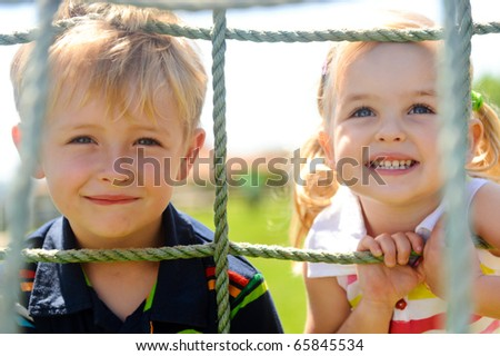 Two young children climbing the net in the playground #65845534