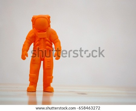 The model printed on a 3d printer. The object in the form of an orange cosmonaut is on the table. Progressive modern additive technology. Copy spase, spase for text. #658463272