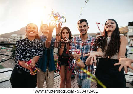 Group of happy young people throwing confetti while enjoying rooftop party. Friends having fun at terrace party.