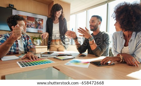 Young and creative start-up team discussing ideas in board room. Group of multi ethnic people during business meeting. Royalty-Free Stock Photo #658472668