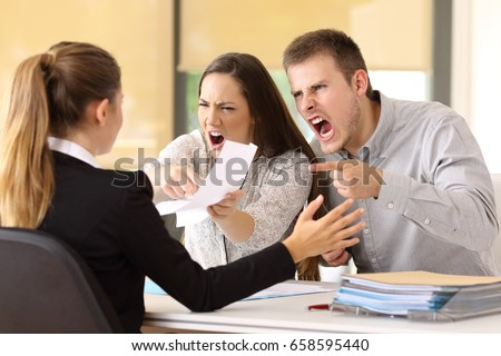 Angry couple claiming and shouting to an office worker  Royalty-Free Stock Photo #658595440