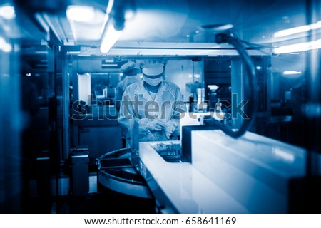 workers and machinery in a solar panel manufacturing industry factory. #658641169