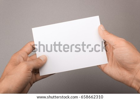 Blank postcard in hands on a gray background. Leaflet A6 mockup Royalty-Free Stock Photo #658662310