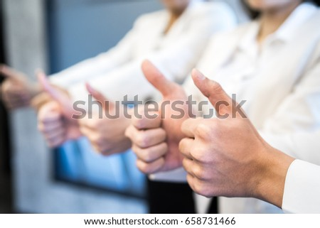 Three business partners keeping thumbs up #658731466