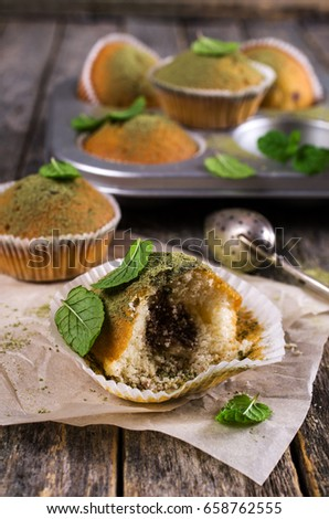 Muffins with green sugar powder and mint on a wooden background. Selective focus. #658762555