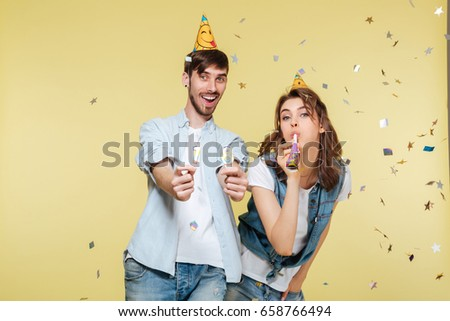 Image of happy brother and sister standing over yellow background. Looking camera.
