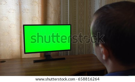 Male Hand With TV Remote Switching Channels On A Green Screen TV Point Of View. #658816264