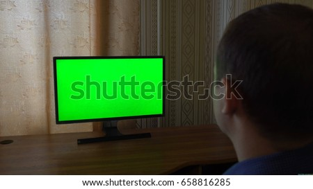 Male Hand With TV Remote Switching Channels On A Green Screen TV Point Of View. #658816285