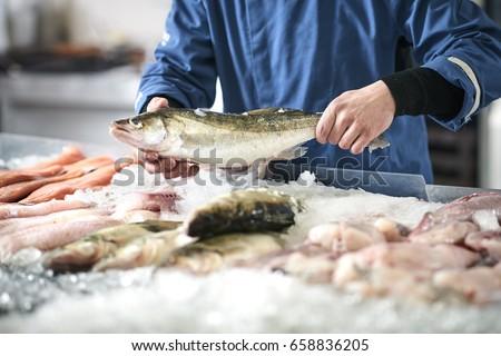 Fishmonger selling fish Royalty-Free Stock Photo #658836205