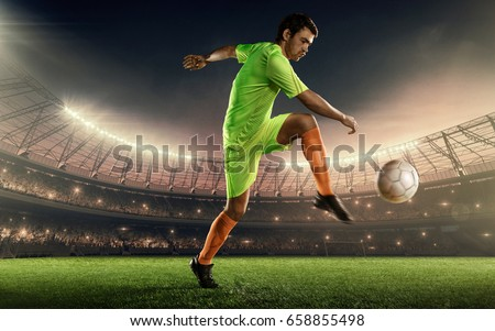 soccer player hits a ball on a soccer stadium with illumination lights and dramatic night sky #658855498