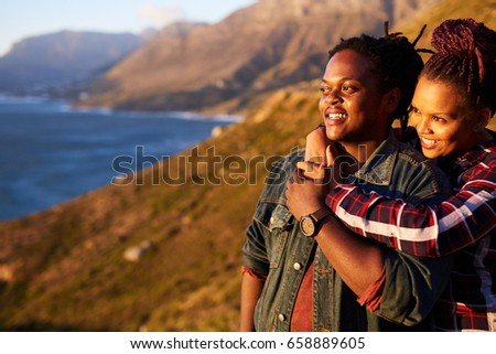 Happy mixed race couple smiling while looking sideways out towards the stunning view of the oceans and mountains in the surrounding landscape, while the woman hold the man from behind. #658889605