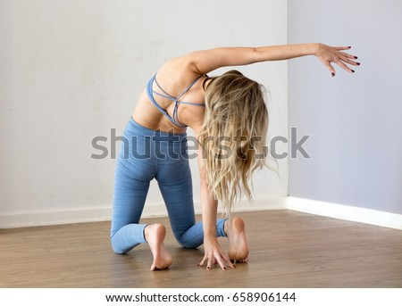 young blonde yoga woman bending backwards performing a yoga pose on a wooden floor in a grey studio  #658906144
